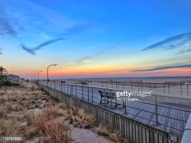 scenic view of beach against sky during sunset - jones beach stock pictures, royalty-free photos & images