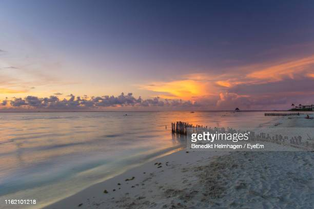 scenic view of beach against sky during sunset - isla mujeres stock pictures, royalty-free photos & images
