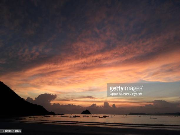 scenic view of beach against sky during sunset - oppie muharti stock pictures, royalty-free photos & images