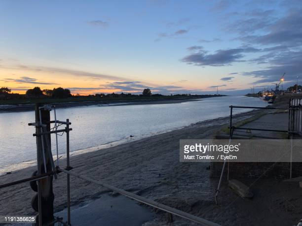 scenic view of beach against sky during sunset - king's lynn stock pictures, royalty-free photos & images