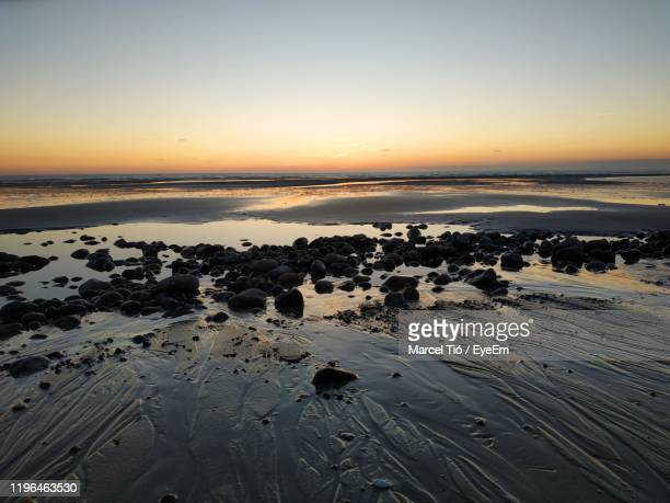 scenic view of beach against sky during sunset - ソム ストックフォトと画像