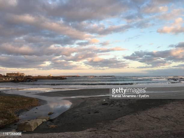 scenic view of beach against sky during sunset - minamino stock pictures, royalty-free photos & images