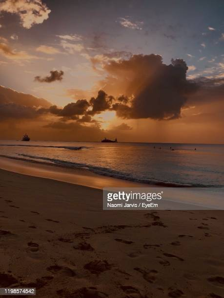 scenic view of beach against sky during sunset - naomi jarvis stock pictures, royalty-free photos & images