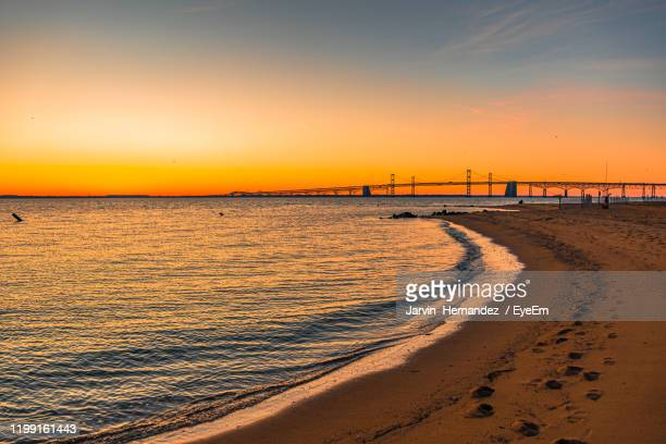 scenic view of beach against sky during sunset - annapolis stock pictures, royalty-free photos & images