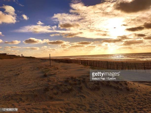 scenic view of beach against sky during sunset - zandvoort stock pictures, royalty-free photos & images