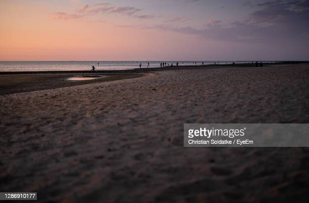 scenic view of beach against sky during sunset - christian soldatke stock pictures, royalty-free photos & images