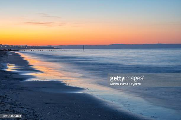 scenic view of beach against sky during sunset - dawn stock pictures, royalty-free photos & images