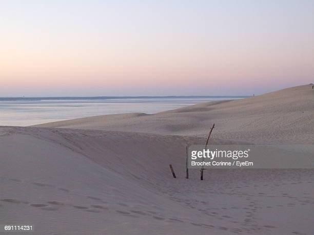 scenic view of beach against sky during sunset - corinne paradis photos et images de collection