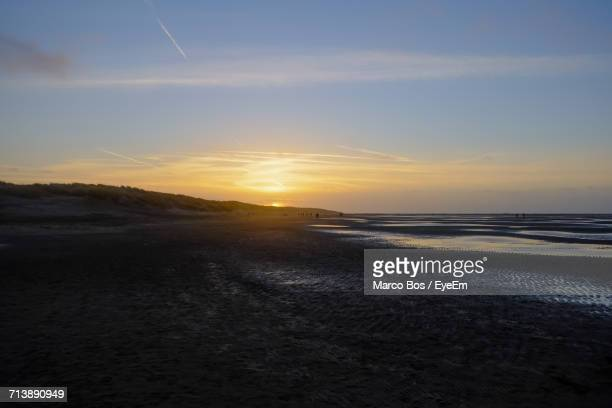 scenic view of beach against sky during sunset - bos stock pictures, royalty-free photos & images
