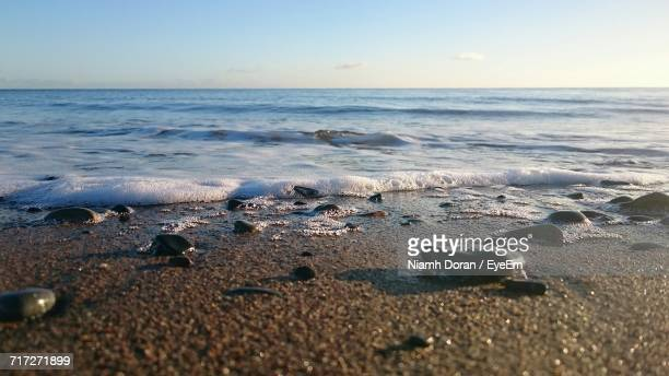 scenic view of beach against sky during sunset - blackrock stock pictures, royalty-free photos & images