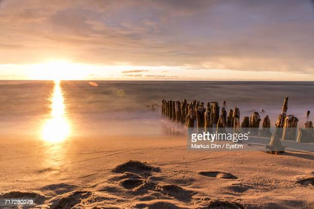 Scenic View Of Beach Against Sky During Sunset