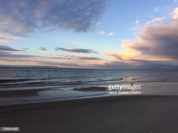 scenic view of beach against sky during sunset - swiatek stock pictures, royalty-free photos & images