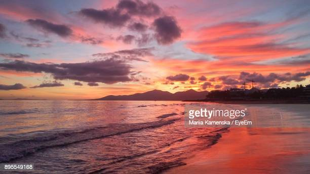 scenic view of beach against sky during sunset - puerto del carmen stock pictures, royalty-free photos & images