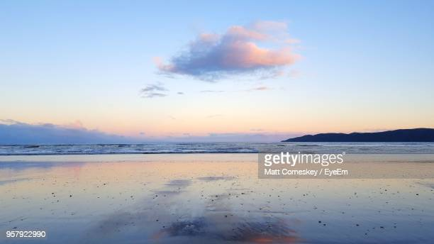 scenic view of beach against sky during sunset - moody sky stock pictures, royalty-free photos & images