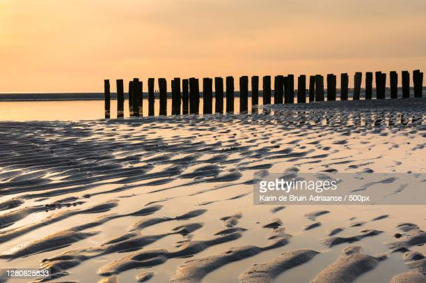 scenic view of beach against sky during sunset,zeeland,netherlands - zonsondergang stock pictures, royalty-free photos & images