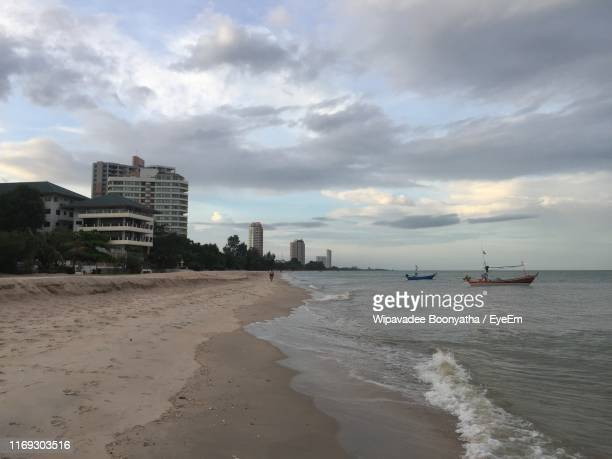 scenic view of beach against sky in city - wipavadee stock photos and pictures
