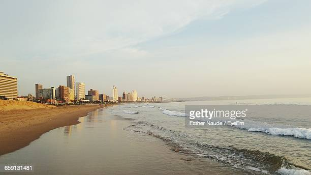 scenic view of beach against sky on sunny day in city - durban beach stock photos and pictures