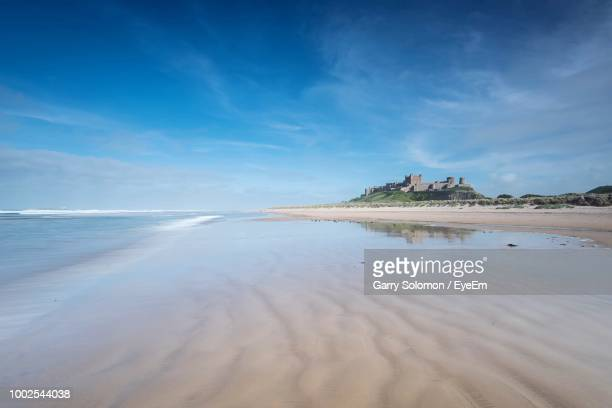 scenic view of beach against sky - northumberland stock pictures, royalty-free photos & images