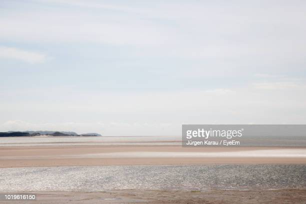scenic view of beach against sky - llanelli stock pictures, royalty-free photos & images