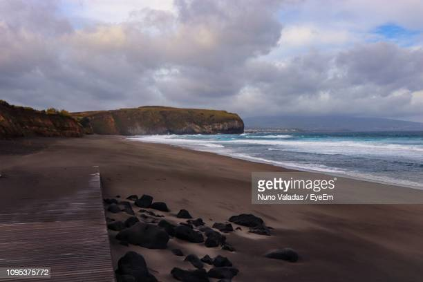 scenic view of beach against sky - punalu'u_beach stock pictures, royalty-free photos & images
