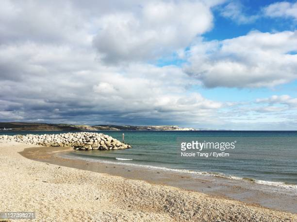 scenic view of beach against sky - weymouth dorset stock pictures, royalty-free photos & images