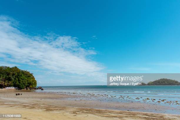 scenic view of beach against sky - jeffrey roque stock photos and pictures