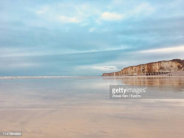 scenic view of beach against sky - beach photos et images de collection