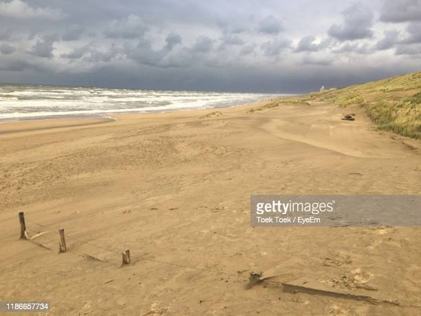 scenic view of beach against sky - noord holland stockfoto's en -beelden