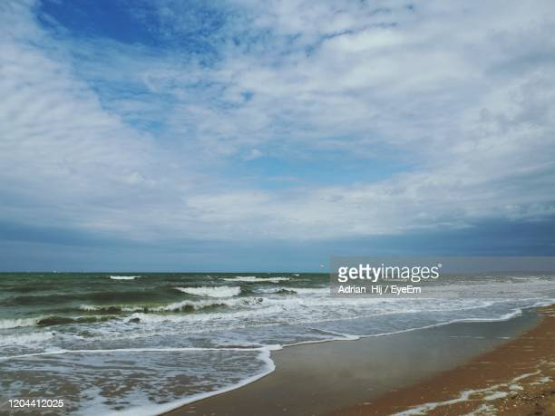 scenic view of beach against sky - calvados stock pictures, royalty-free photos & images