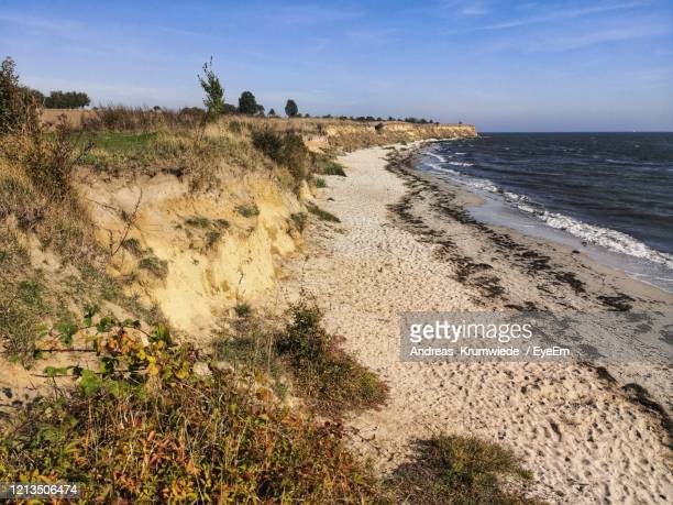 scenic view of beach against sky - fehmarn stock-fotos und bilder