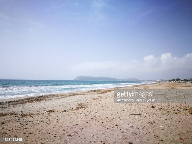 scenic view of beach against sky - rocky coastline stock pictures, royalty-free photos & images