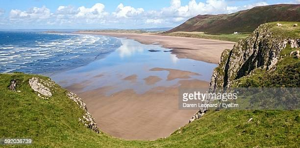 scenic view of beach against sky - gower peninsula stock photos and pictures