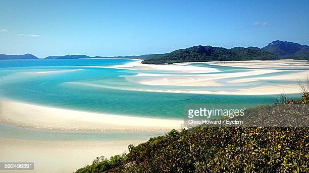 scenic view of beach against sky - whitehaven beach stock-fotos und bilder