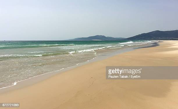 scenic view of beach against sky - paulien tabak stock pictures, royalty-free photos & images