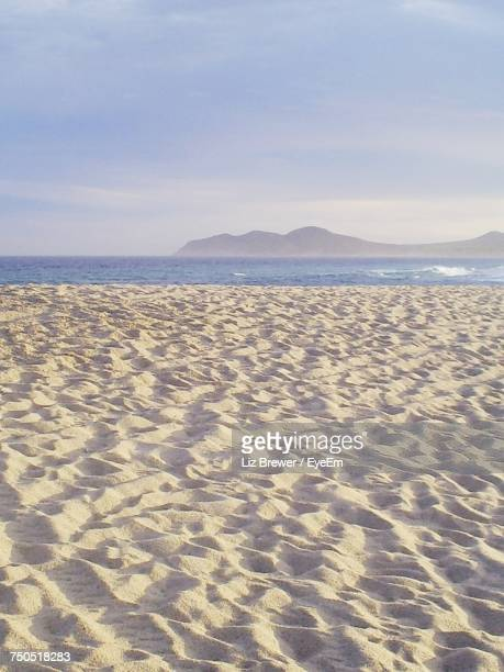 scenic view of beach against sky - liz brewer stock photos and pictures