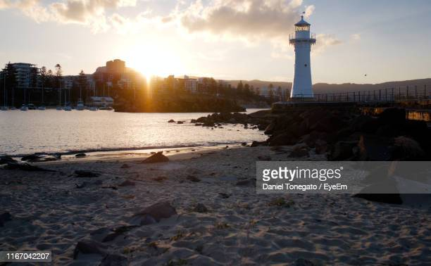 scenic view of beach and buildings against sky during sunset - wollongong stock pictures, royalty-free photos & images