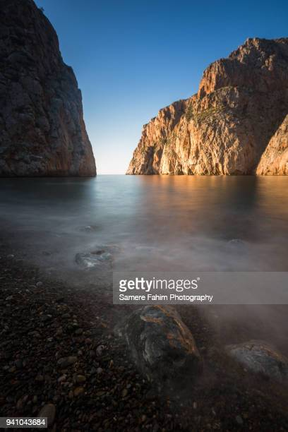 scenic view of beach and rochy cliff against blue sky - samere fahim stock photos and pictures