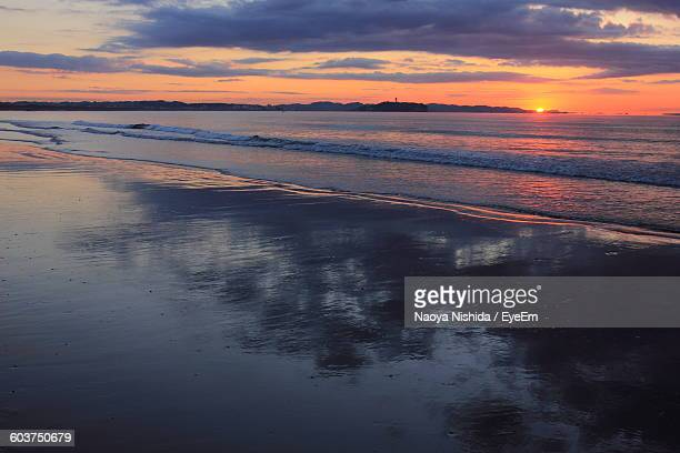 Scenic View Of Beach And Sea Against Cloudy Sky During Sunset