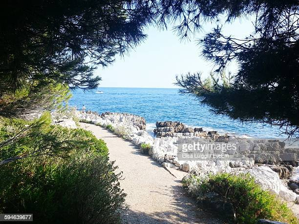 scenic view of beach and sea against sky - antibes stock photos and pictures