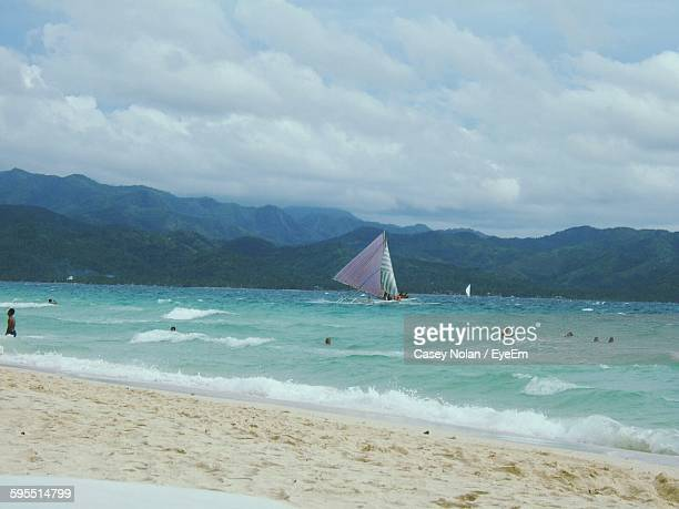 scenic view of beach and sea by mountains against cloudy sky - casey nolan stock pictures, royalty-free photos & images