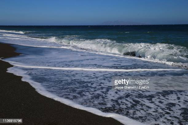 scenic view of beach and sea wave against clear sky - punalu'u_beach stock pictures, royalty-free photos & images
