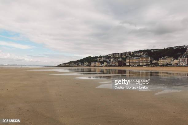 scenic view of beach by buildings against cloudy sky - trouville sur mer stock pictures, royalty-free photos & images