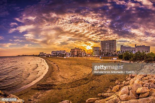 Scenic View Of Beach By Cityscape Against Cloudy Sky During Sunset