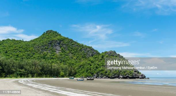 scenic view of beach by mountains against sky - prachuap khiri khan province stock pictures, royalty-free photos & images