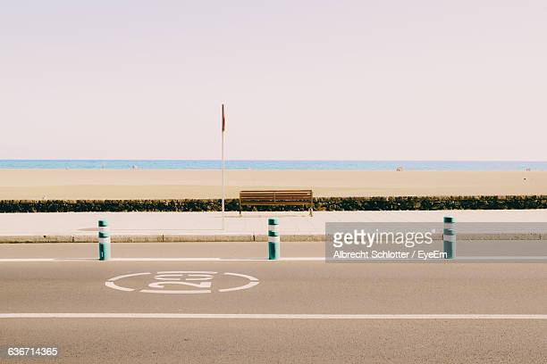 Scenic View Of Beach In Front Of Road Against Sky On Sunny Day