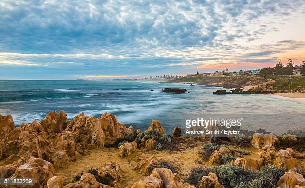 Scenic view of beach rocks against cloudy sky
