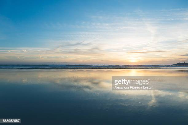 Scenic View Of Beach With Reflection Of Sky During Sunset