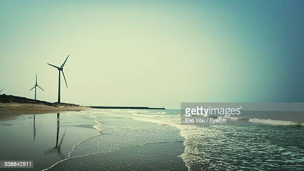 Scenic View Of Beach With Windmill Against Clear Sky