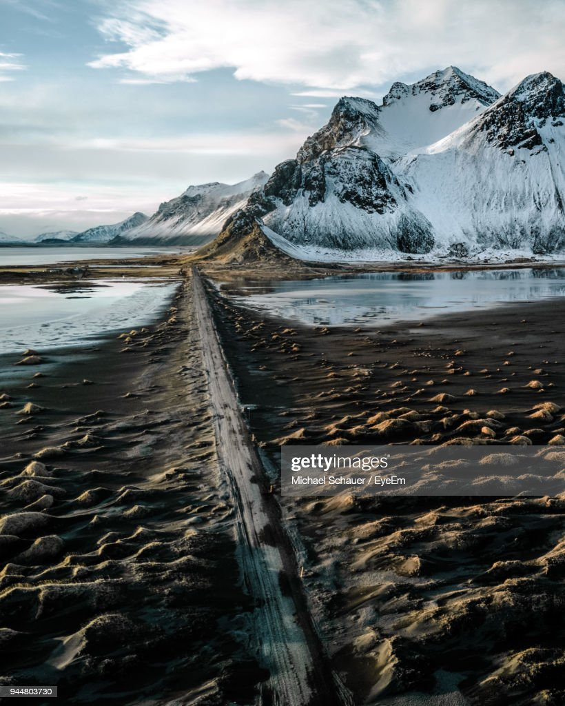 Scenic View Of Black Sand Beach And Snowcapped Mountain Against Sky : Stock Photo