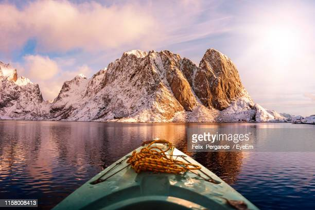 scenic view of boat in lake against snowcapped mountains and sky - tranquil scene stock pictures, royalty-free photos & images
